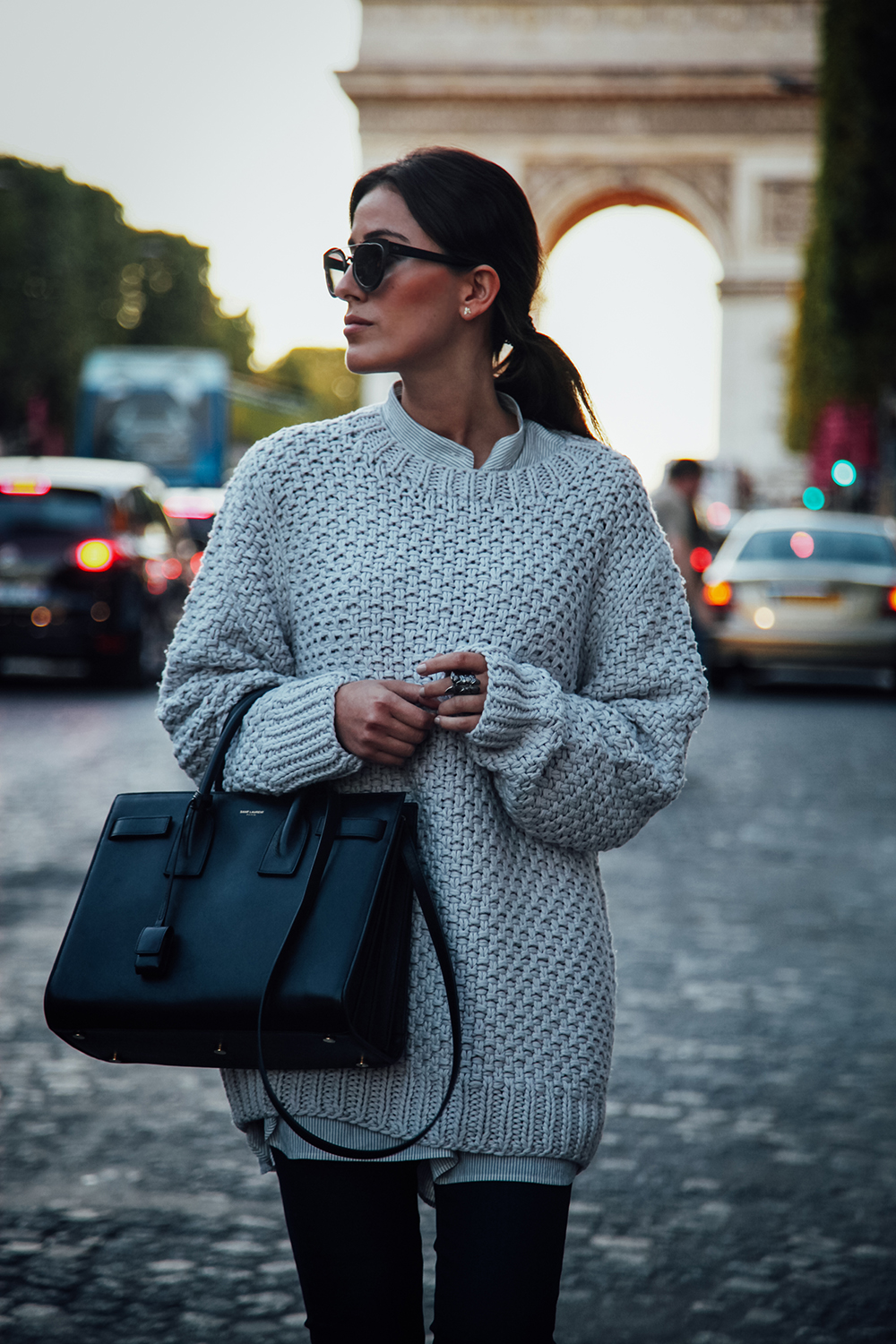 Sylvia Haghjoo wears a cute oversized knit pullover with a striped shirt and simple black jeans. Sweater: La Roca Village, Jewlery: Georg Jensen, Shades: Dior, Bag: Saint Laurent, Blouse: Tibi.