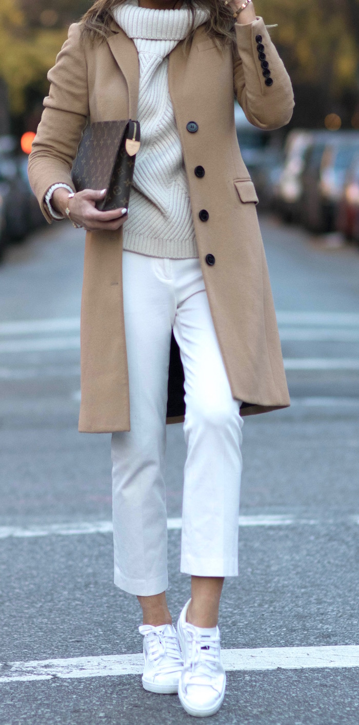 Knitted sweaters add a wintery feel to an all white look. Brooke Carrie Hil wears a gorgeous beige knit with white cigarette trousers and sneakers, all brought together with a camel overcoat. Coat: Burberry, Shoes: Bloomingdales, Trousers: J Crew, Sweater: Rag & Bone.