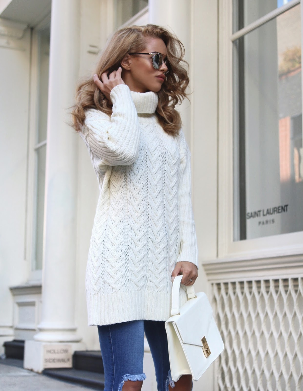This chunky white turtle neck style knit makes a great match with simple denim jeans. Alternatively, wearing a pale knit sweater with black jeans would make for an edgy monochrome look. Via Nada Adelle. Jumper: Runway 96, Ripped Jeans: Fashion Nova, Sunglasses: Yesstyle, Hand Bag/Heels: Luxe To Kill.