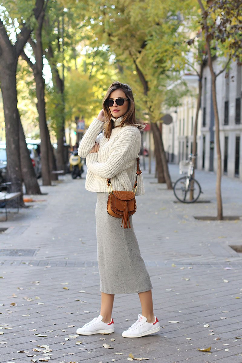 Knitwear can be worn with sneakers for a more casual, unconventional style. Silvia Zamora wears a grey knit midi skirt with white adidas trainers and a cropped cream knit sweater. Coat: Purificación García, Skirt: Mango, Sweater: Zara, Sneakers: Adidas Stan Smith, Bag: Chloé Hudson.