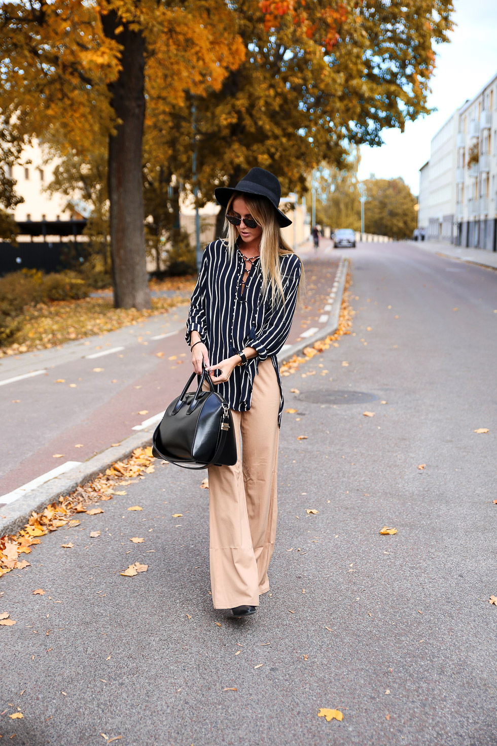 Kristin Sundberg wears a gorgeous lace up tunic with flared nude trousers and a wide brimmed hat. Trousers: Saboskirt, Top: Faithfull The Brand, Hat: Lindex.