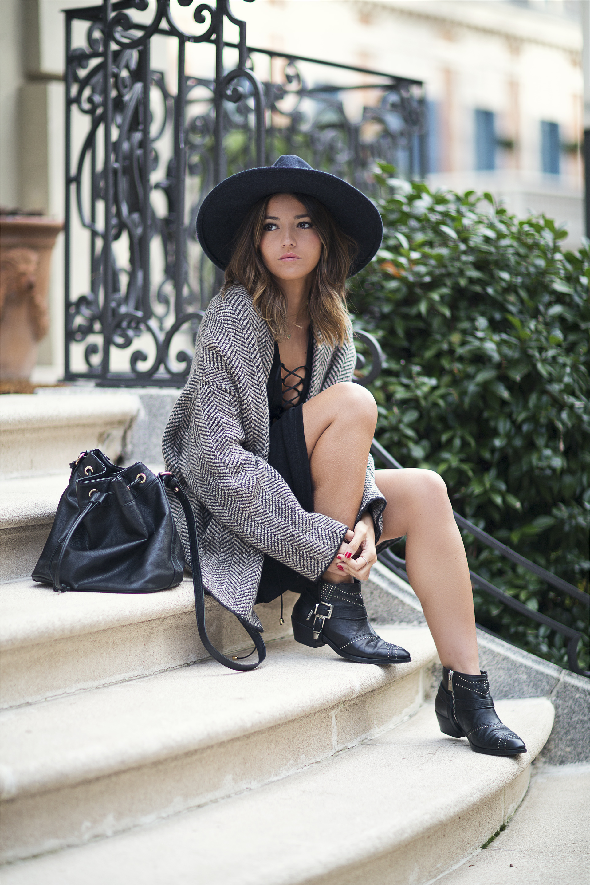 Lace up detailing looks great on a cute mini dress such as this one worn by Alexandra Pereira. Pairing the dress with an oversized tweed blazer and studded ankle boots, this look is edgy and stylish. Dress: Wolflamb, Booties: Anine Bing, Coat: Zara, Bag: Mango, Hat: H&M.