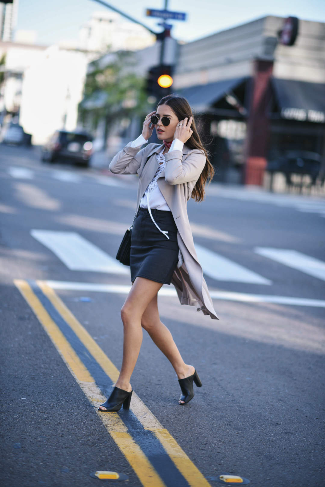 Lace up detailing will always look gorgeously feminine worn on a simple blouse! Paola Alberdi pairs such a lace up blouse with a black mini skirt and a beige overcoat. Blouse: The Kooples, Coat: Nordstrom.