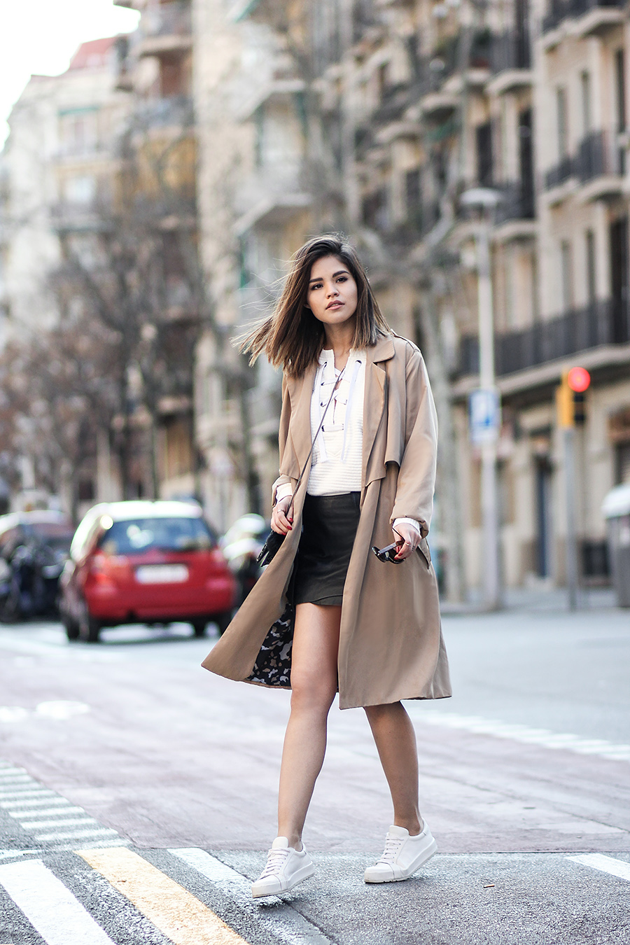 Adriana Gastélum pairs a lace up sweater with a mini skirt and a camel coloured trench coat to create a sophisticated and stylish aesthetic for everyday wear. Sweater: Shein, Coat: Zara, Skirt: Maje, Sneakers: Jil Sander.