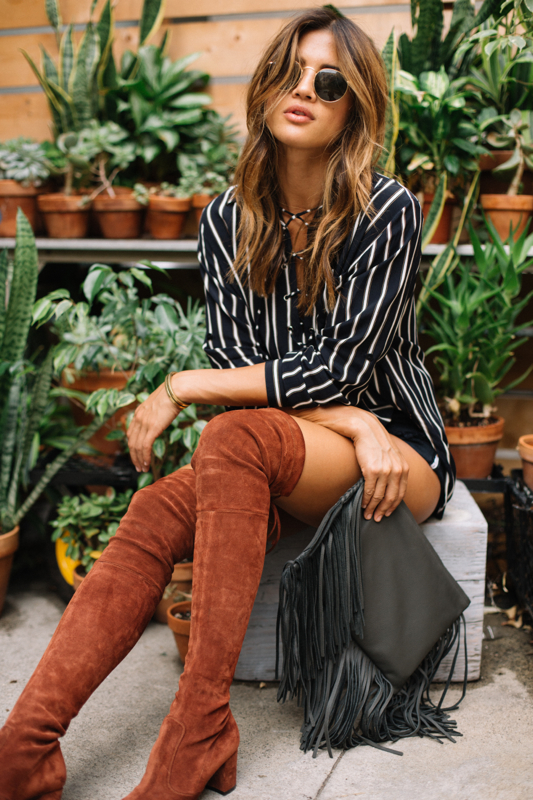 We love Rachel Barnes' striped lace up blouse. Wear a similar number with rusty over the knee boots and a fringed leather bag to recreate this look. Top: Faithfull the Brand, Boots: Jean Michel, Shorts: One Teaspoon, Bag: Jennifer Haley.