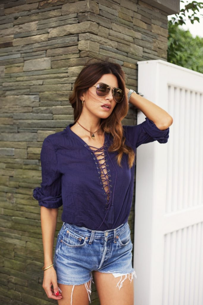 Negin Mirsalehi wears cute lace up blouse with fringed vintage denim shorts.  Blouse: Revolve Clothing.