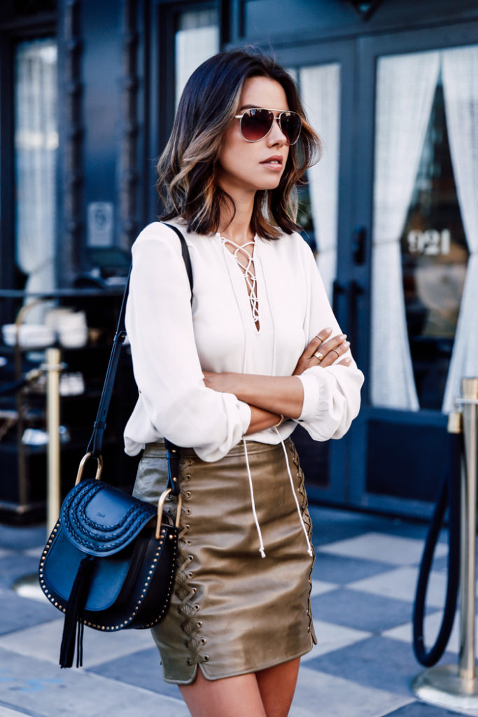 Annabelle Fleur rocks the lace up trend on both her metallic skirt and cute white blouse.   Top/Skirt: Rebecca Minkoff.