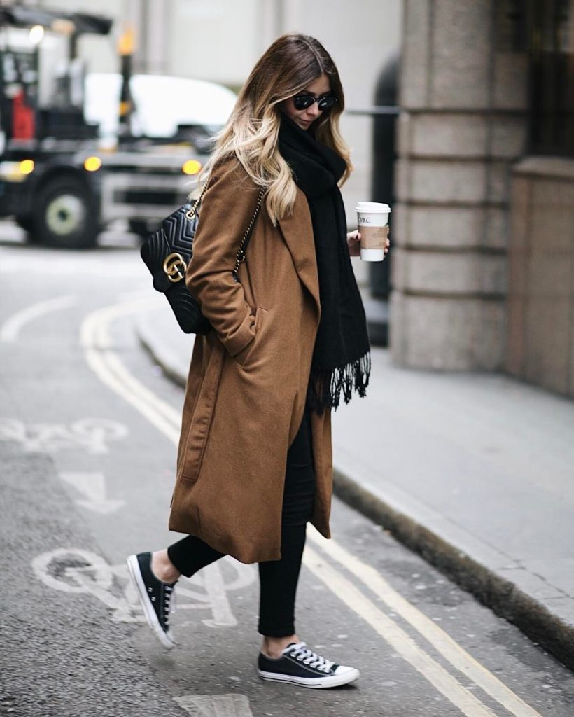 Emma Hill wears black and white converse with black jeans, an oversized black frayed-end scarf, and a cosy brown overcoat. This style is finished off with a leather handbag and shades. Brands not specified.