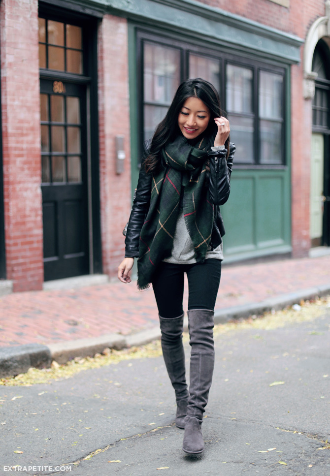 Jean Wang wears grey over the knee boot with an authentic tartan scarf and a leather jacket.  Scarf: Sole Society, Tee: Loft, Jacket: BlankNYC, Jeans: J Brand, Boots: Stuart Weizman.