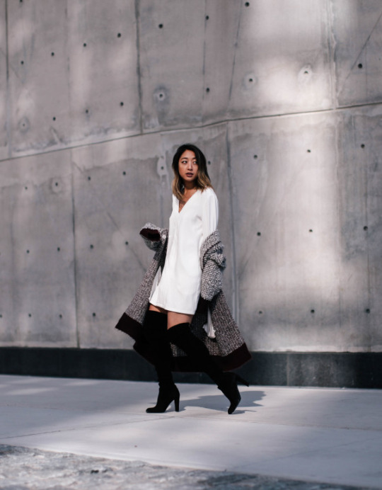 Serena Goh wears heeled over the knee boots with a cute V neck dress and a long cardigan.   Coat: Elizabeth And James, Dress: Fifth Label, Boots: Stuart Weitzman.