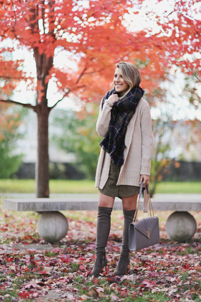 Stephanie Sterjovski wears a pair of over the knee boots with a khaki shirt dress and cute knitted cardigan.   Blanket Scarf: Nordstrom, Shirtdress/Cardigan: Forever 21, Boots: Joie.