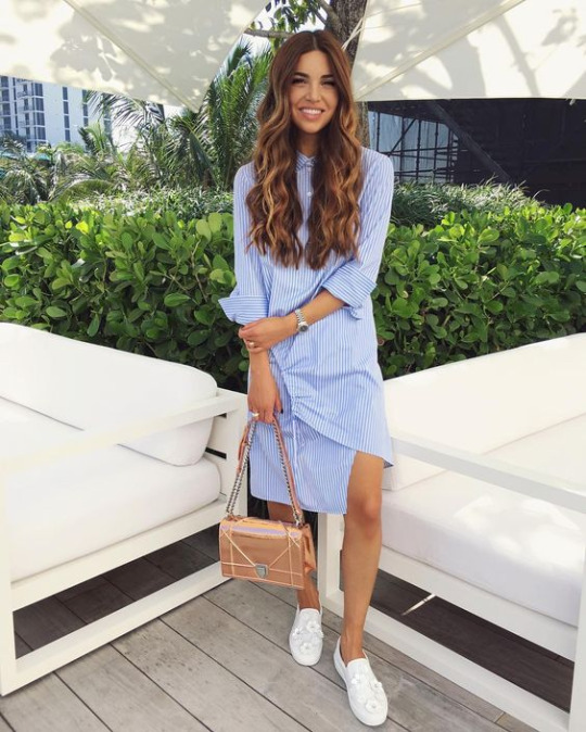 Negin Mirsalehi wears a super cute blue and white pinstripe shirt dress, paired with white loafer style shoes and minimal jewellery for an effortlessly summery style.   Dress: Miami Design District, Bag: Dior.