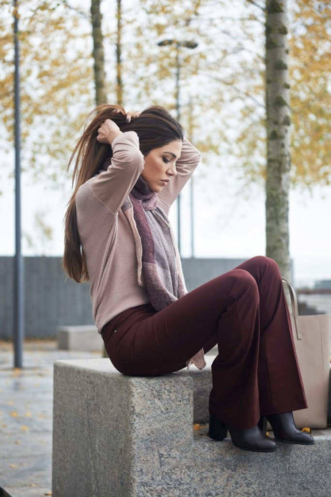 Negin Mirsalehi wears a gorgeous pair of dark flares with an oversized scarf and heeled Chelsea boots.   Outfit: Taranko.