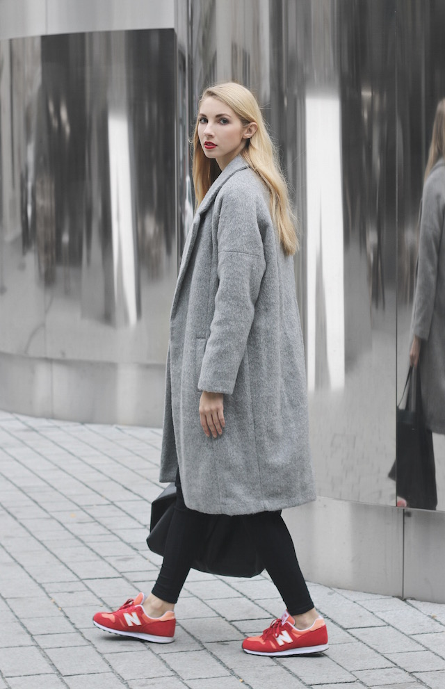 This grey fur coat looks great paired with red New Balance sneakers and  casual black jeans
