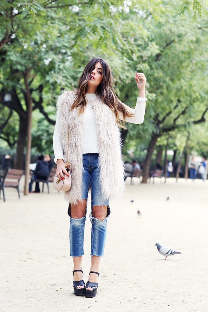 Aida Domenech wears mega distressed jeans with a fluffy sleeveless coat and platform sandals.   Vest: Pull&Bear, Sweater and jeans: Zara, Bag: Chloe , Shoes: Jeffrey Campbell.