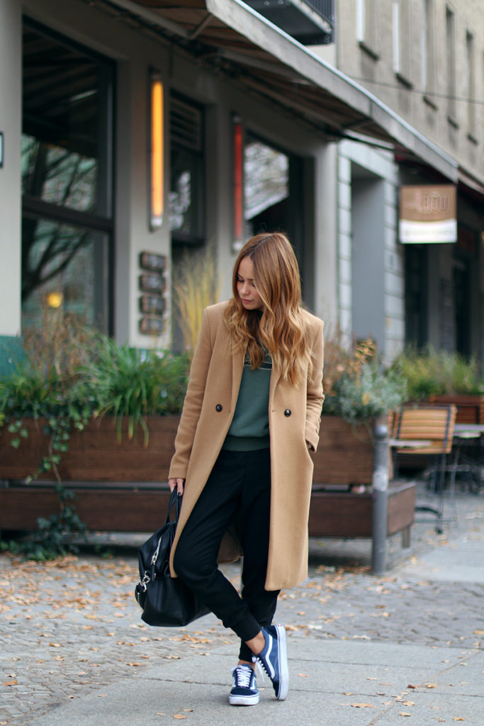 Elena Pellicano looks cute and casual in a camel overcoat and black drop crotch trousers.   Coat: Promod, Sweater: Isabel Marant, Sneakers: Vans. Elena Pellicano looks cute and casual in a camel overcoat and black drop crotch trousers.   Coat: Promod, Sweater: Isabel Marant, Sneakers: Vans.