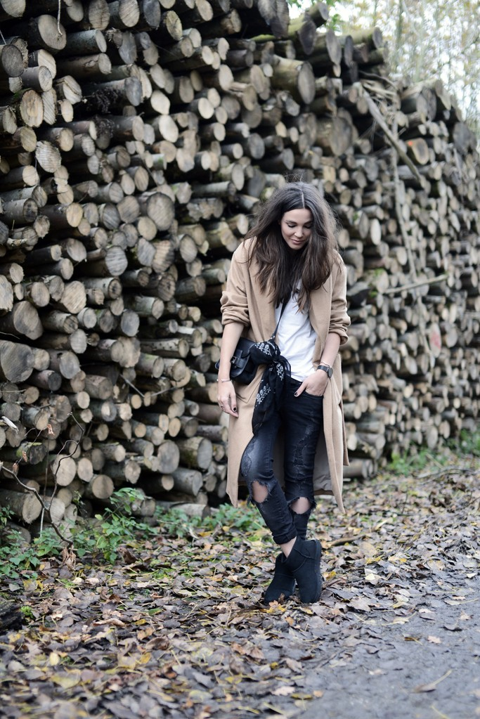 Cindy Van Der Heyden rocks the destroyed jeans trend, wearing a pair of black skinnies with a plain white tee and a camel overcoat. Coat: Mango, Jeans: H&M, Boots: Ugg.
