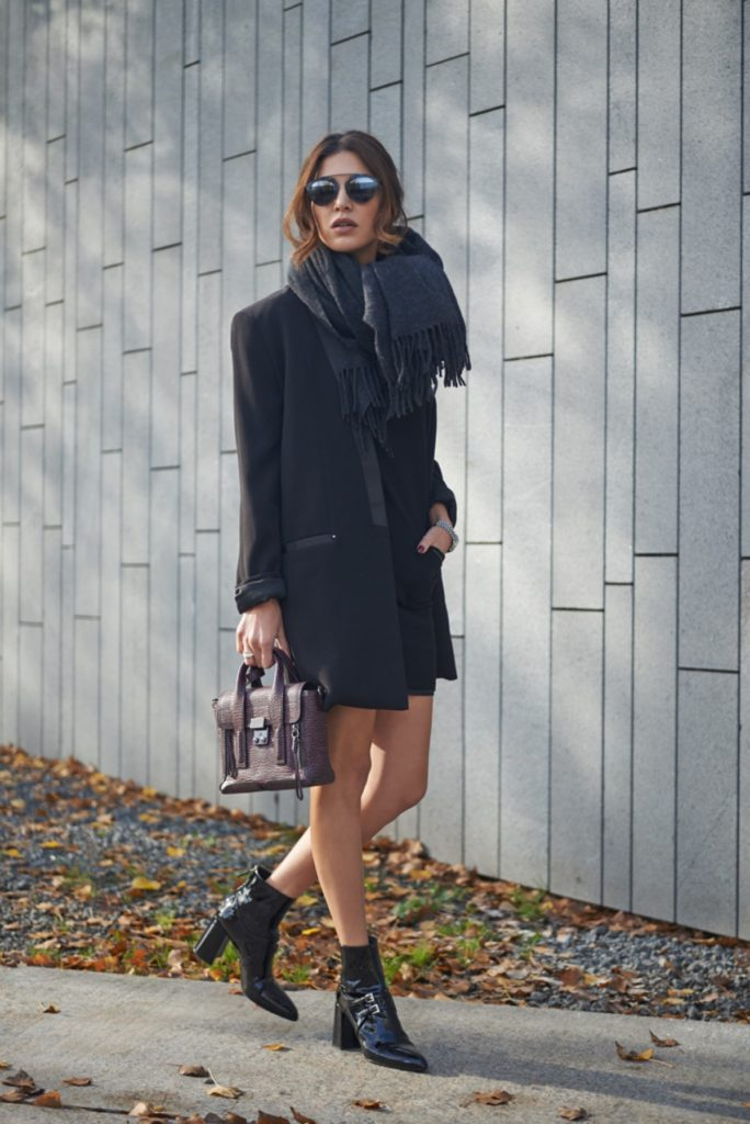 Negin Mirsalehi wears a black knitted dress with an oversized androgynous style blazer and trendy patent ankle boots.  Dress: Via Delle Perle.