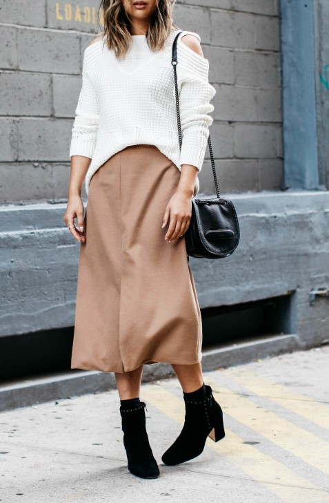 Serena Goh wears a beige maxi skirt with a shoulderless knit sweater and ankle boots.  Sweater: Y Yigal, Skirt: SVILU, Boots: Felicia.