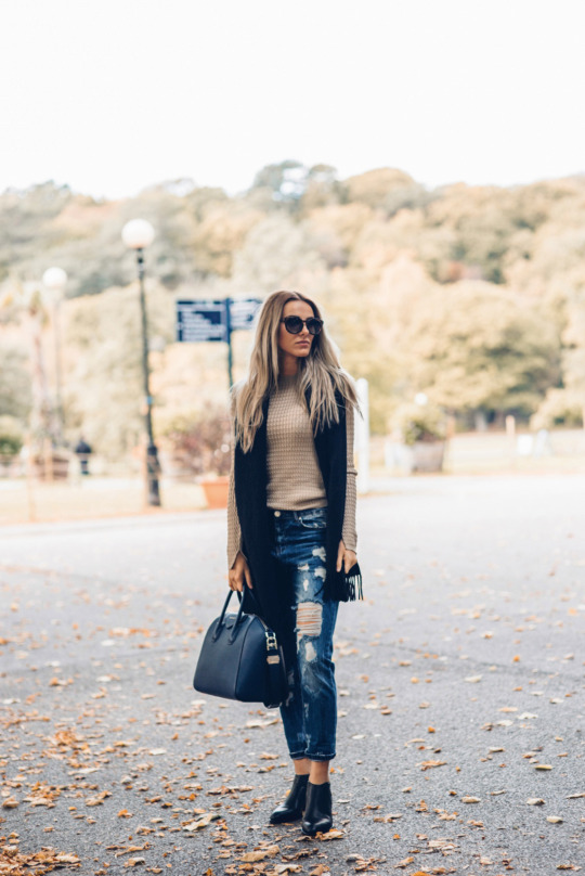 Sendi Skopljak wears the distressed jeans trend with a beige knitted jumper and a black fringed scarf.   Top/Jeans: Chiquelle, Shoes: Alexander Wang, Bag: Givency.