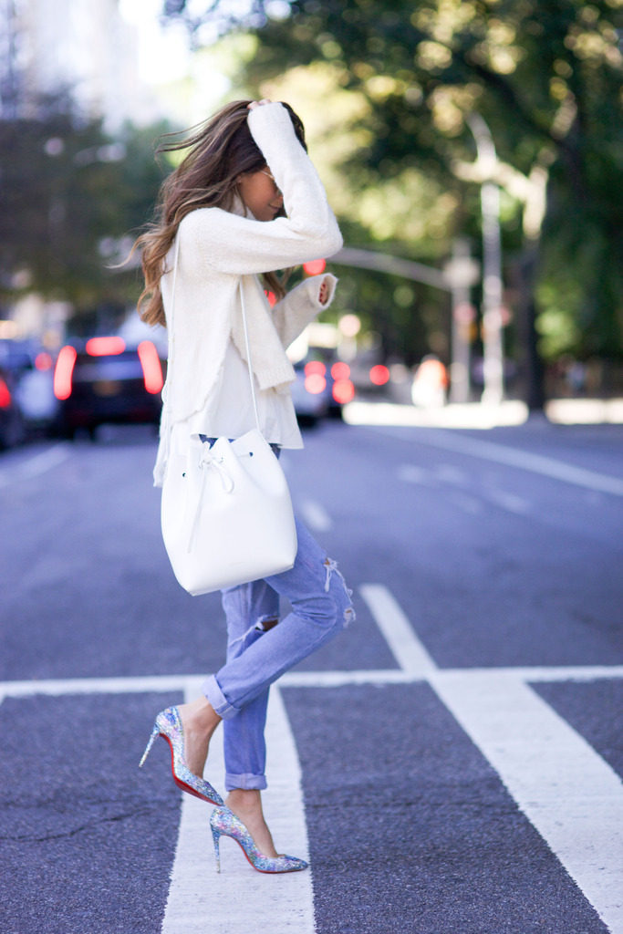 Arielle Nachami wears a pair of cute sparkly heels with pastel jeans and a simple white knitted top.   Jeans: Redone, Shoes: Christian Louboutin, Sweater: Tibi, Sunglasses: Westward Leaning, Bag: Mansur Gavriel.