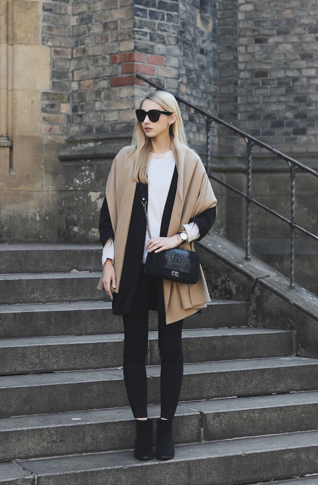 Scarves make great additions to casual fall outfits. Pavlína Jágrová wears a large camel scarf over her black coat and matching black jeans. Coat/Scarf: H&M, Jeans: Lindex, Sweater: Blazek.