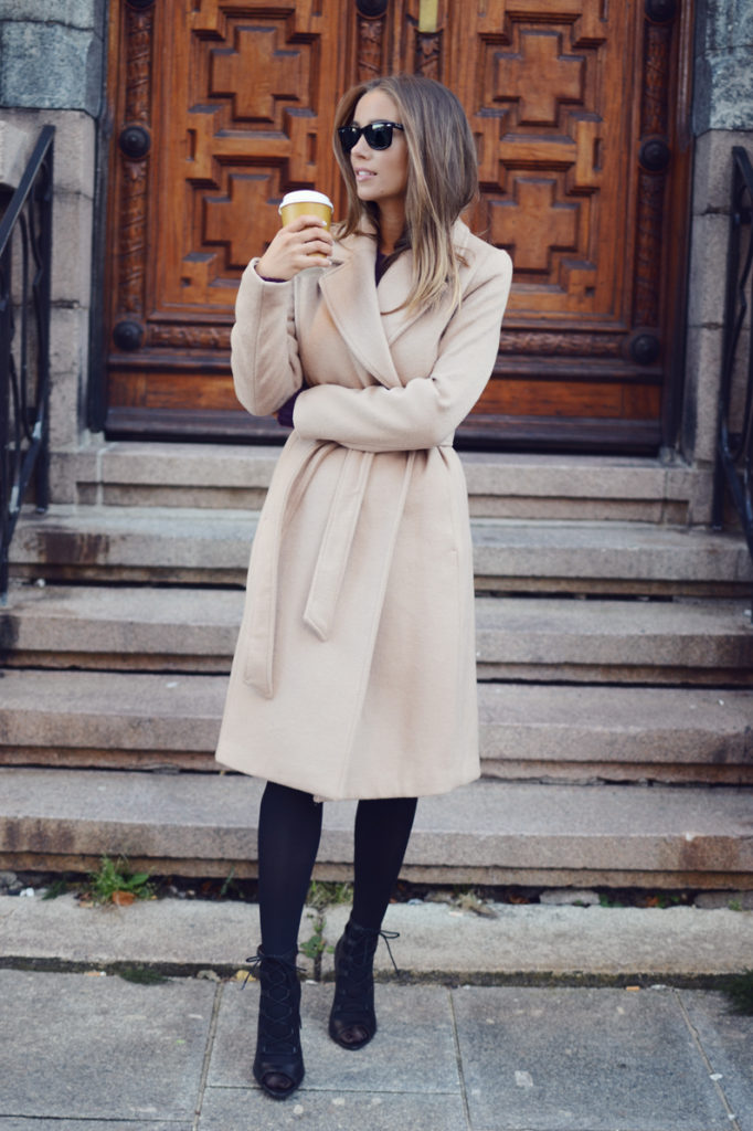 Emilie Tømmerberg rocks the robe coat trend, paring this cream coat with funky heels and black tights.   Coat: H&M.