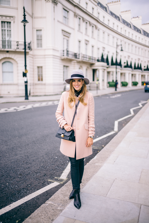 Julia Engel looks feminine and elegant in this frilled pink coat and a pair of skinny black jeans. Coat: Miu Miu, Boots: Acne Studios.