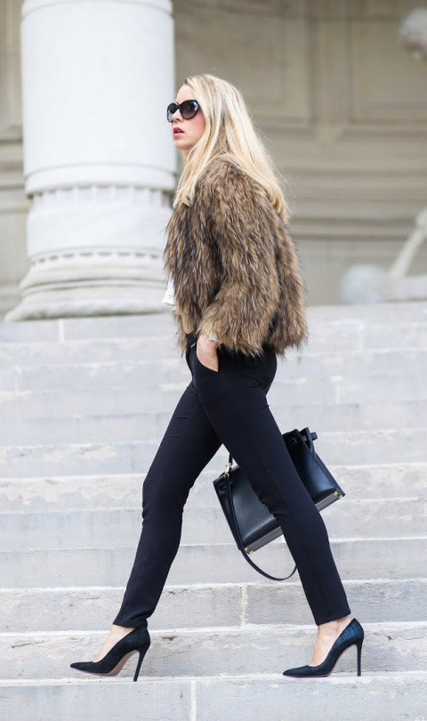 Caroline Louis pairs a fur coat with sleek cigarette trousers and a pair of black heels. Fur: Vintage, Top: Iris and Ink, Trousers: Five Jeans.