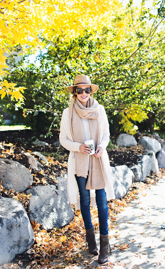 Christine Andrew wears casual jeans and a long cardigan, accessorising with an oversized scarf and a stylish fedora.   Boots: Vince Camuto, Cardigan: Forever21, Knit Scarf: Ily Couture.
