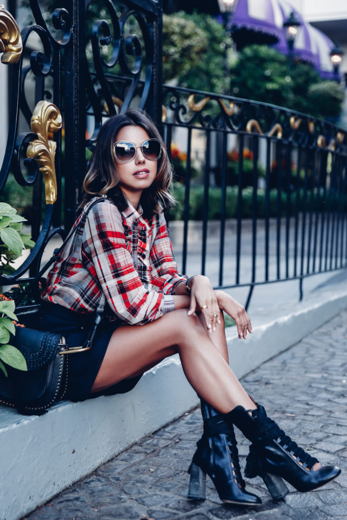 Annabelle Fleur wears a stylish plaid blouse with black mini shorts and ribbon-laces boots.   Shorts: Isabel Marant, Shirt: Paul & Joe, Boots: Harper.