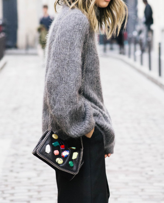 Serena Goh accessorises a grey knitted jumper and black skirt with a Stella McCartney gem-detailed handbag. Sweater: COS, Trousers: French Connection, Bag: Stella McCartney.