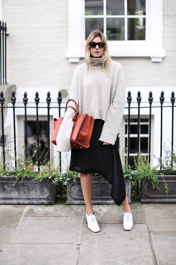 Camille Charriere wears an extra-long sleeve pale knitted pullover with a black skirt and boots. Knit: Celine, Skirt: McQ Alexander McQueen.