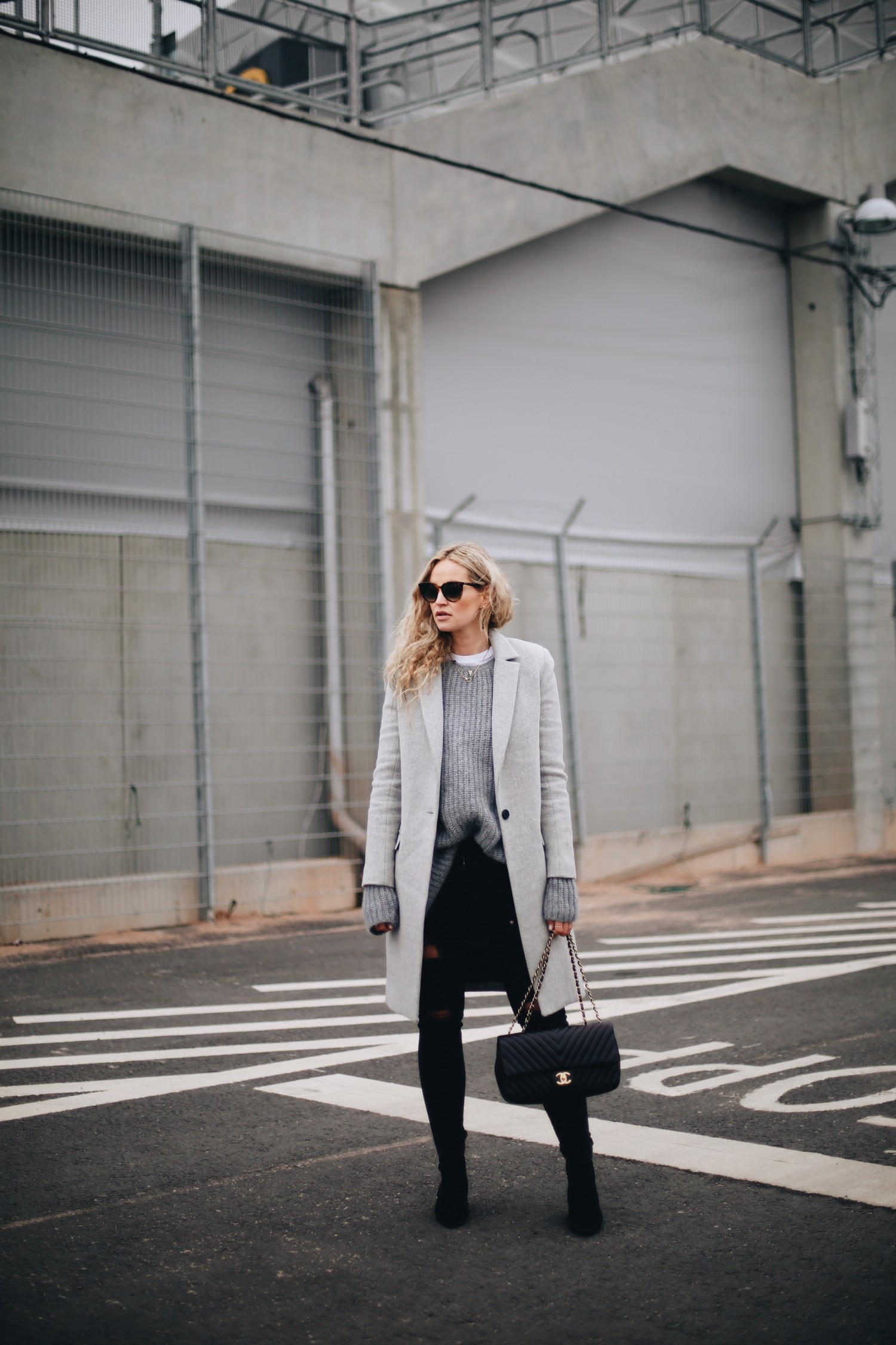 An oversized sweater is the perfect way to wear the extra long sleeves trend. Anouk Yve looks effortlessly stylish in this grey knit sweater and pale overcoat worn with distressed black jeans. Coat: America Retro, Knit: Cos, Tee: Asos, Jeans: Zara, Bag: Chanel.