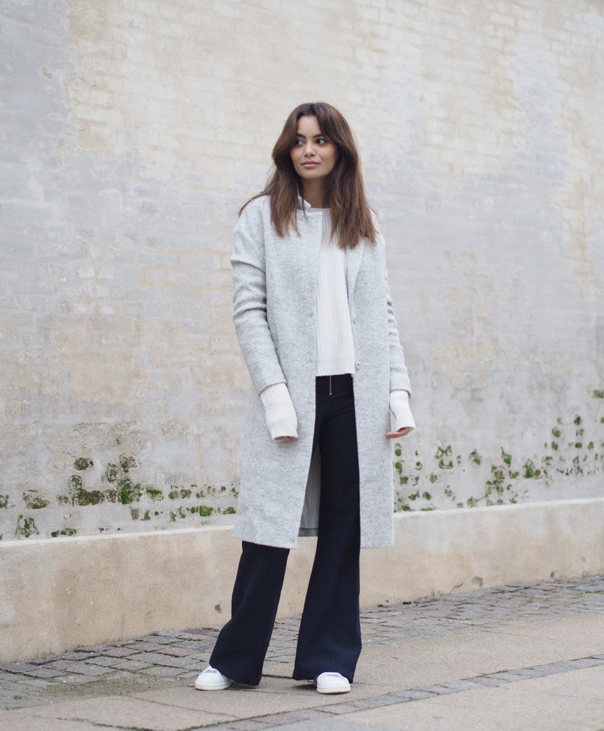 Funda Christophersen wears an extra long sleeve sweater with a pale grey overcoat and wide leg trousers.   Coat/Trousers: Second female, Sneakers: Adidas.
