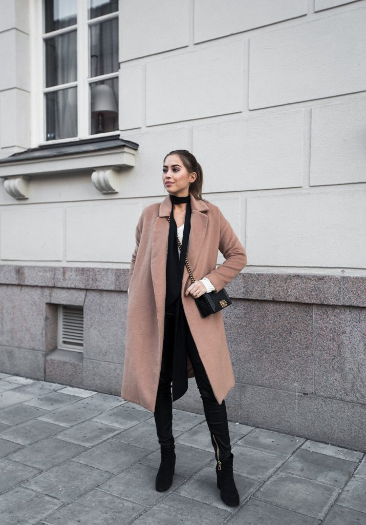 Worn with a classic camel coat and black jeans, this skinny scarf adds a whole new level of elegance to Kenza Zouiten's look. We recommend you wear a scarf like this with a block coloured outfit to create a striking contrast in tones.   Sweater: Ivyrevel, Coat: Make Way, Trousers: HMxBalmain.