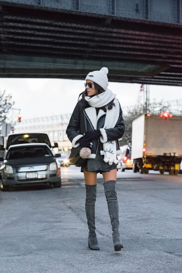Christine Andrew looks cosy and casual in this winter outfit, consisting of thigh high suede boots, a leather shearling coat, and a hat and scarf combination. We love this style! Coat: Kate Spade, Boots: Stuart Weitzman.