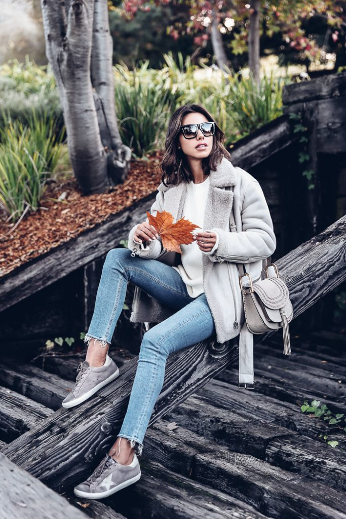 Annabelle Fleur is a vision in this classic cosy, winter style consisting of a shearling trim coat paired with distressed denim jeans and suede sneakers. Throw on a pair of shades to make this outfit the perfect sunny autumn sunday look!  Coat: Acne, Pullover: Phillip Lim, Sneakers: Golden Goose.