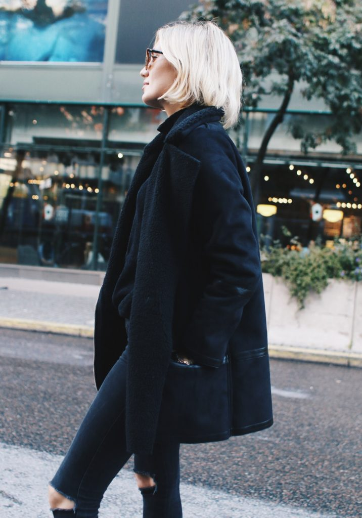 Josefin Dahlberg rocks all black in this shearling coat and ripped jeans.  Jacket: Second Female, Polo: Bik Bok, Jeans: Diesel, Boots: DinSko.