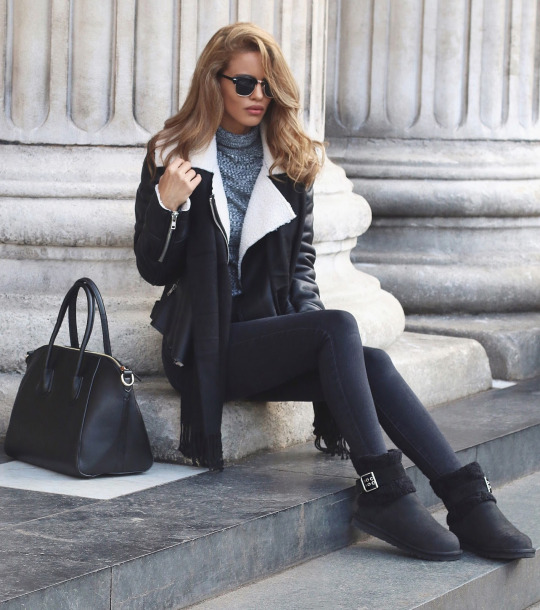 Nada Adelle wears a leather shearling jacket with a polo neck sweater and a black tassel scarf.  Boots: Ugg, Shearling Jacket: Glmaorous, Roll Neck Jumper: Topshop, Tassel Scarf: H&M.