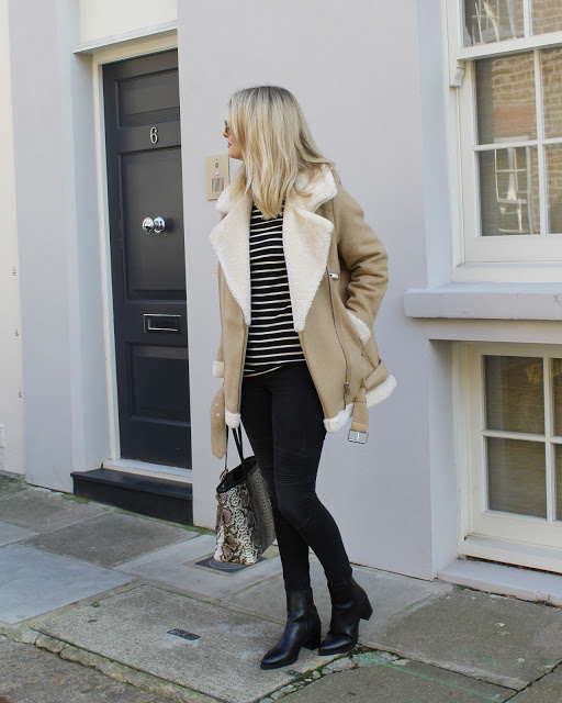Chrissabella Pink wears a classic camel shearling trim jacket with black jeans and a faux crocodile skin bag.   Top: Petit Bateau, Coat: Asos.