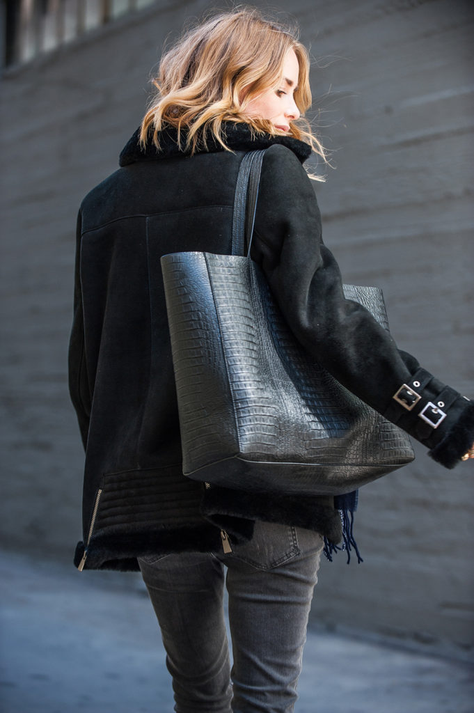 Anna Maria wears a black shearling coat with skinny jeans and accessorises with a faux crocodile skin handbag.   Coat/Jeans/Bag: Anine Bing.