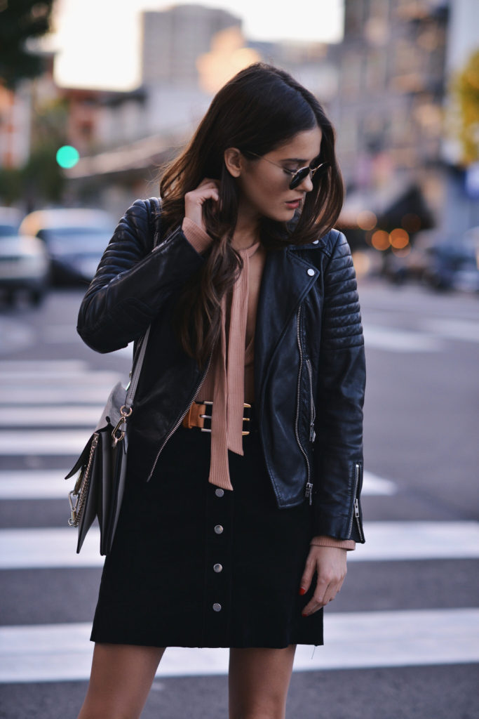 A skinny scarf makes the perfect addition to a plunge neck leotard or bodysuit, Paola Alberdi wears this look with a button up skirt and classic leather jacket.   Jacket: All Saints,  Body Suit: Reformation Grady, Belt: Maison Marigiela, Skirt: Forever 21, Handbag: Chloe Faye.