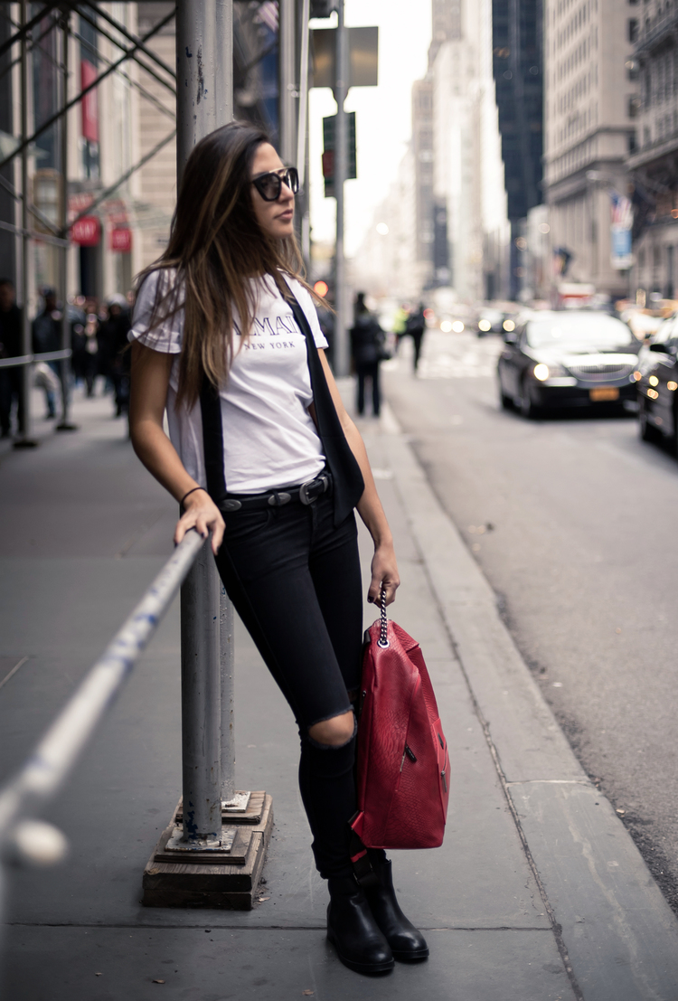 Raquel Paiva wears a simple black skinny scarf with a casual outfit consisting of a white graphic tee and ripped black jeans, pulled together with a cute red backpack. We love this use of the scarf to add edge and dimension to the look. Scarf: Zara, Backpack: FlatIron, Sunglasses: Prada, Belt: Forever21, T-shirt: Balmain x H&M, Jeans: H&M, Boots: Steve Madden.