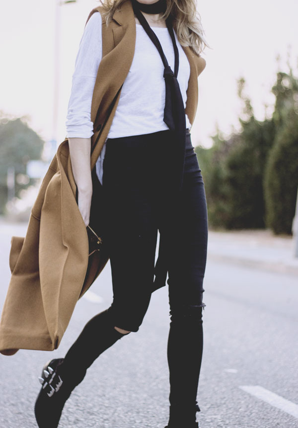 Isabel Sellés is wearing the skinny scarf trend in a sleek and stylish manner, combining a sleeveless camel maxi coat and a plain white blouse with a black tie style scarf. We love this chic look! Coat/Scarf: Zar, Shirt: Lara Talbot, Jeans: Topshop, Boots: Bershka.