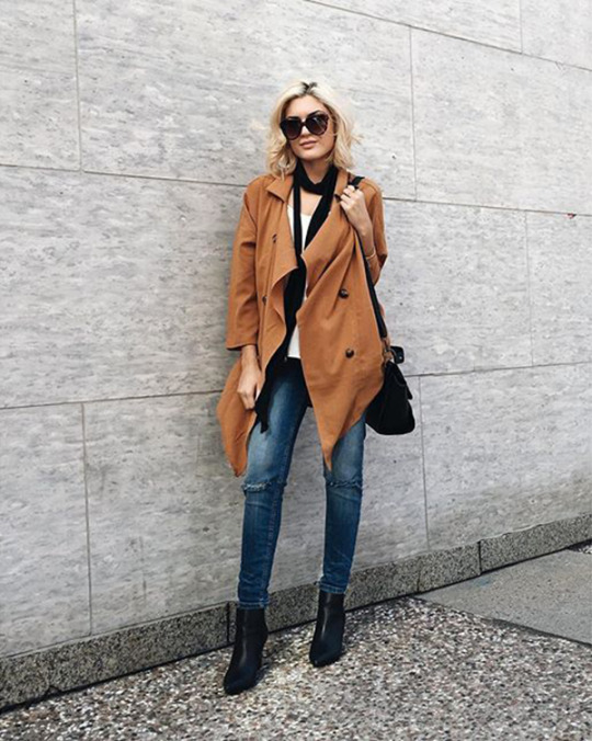 Emily Luciano wears a skinny scarf with casual jeans and a gorgeous camel trench coat. Brands not specified.