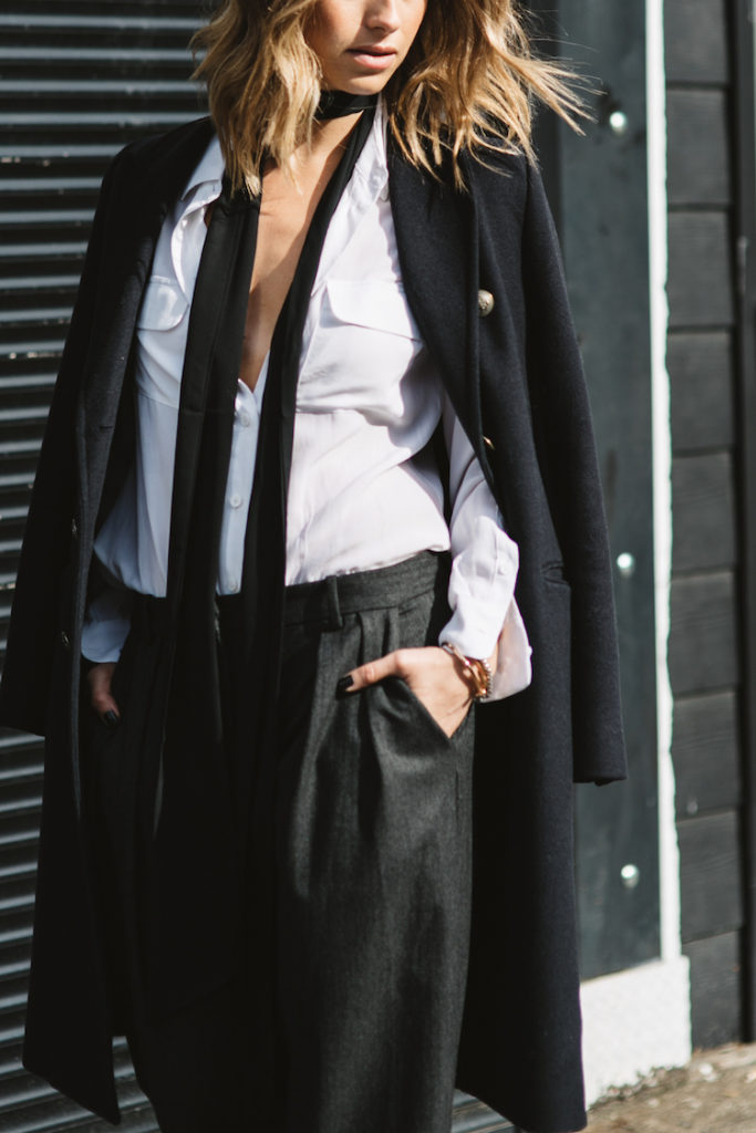 Jill Lansky wears the androgynous trend in a black overcoat, slacks and a skinny scarf.   Coat: Aritzia, Blouse: Equipment, Trousers: Zara, Scarf: ASOS.