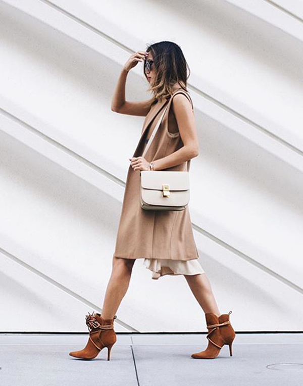 Aimee Song looks casual and elegant in a tan sleeveless jacket and brown ankle boots.   Brands not specified.