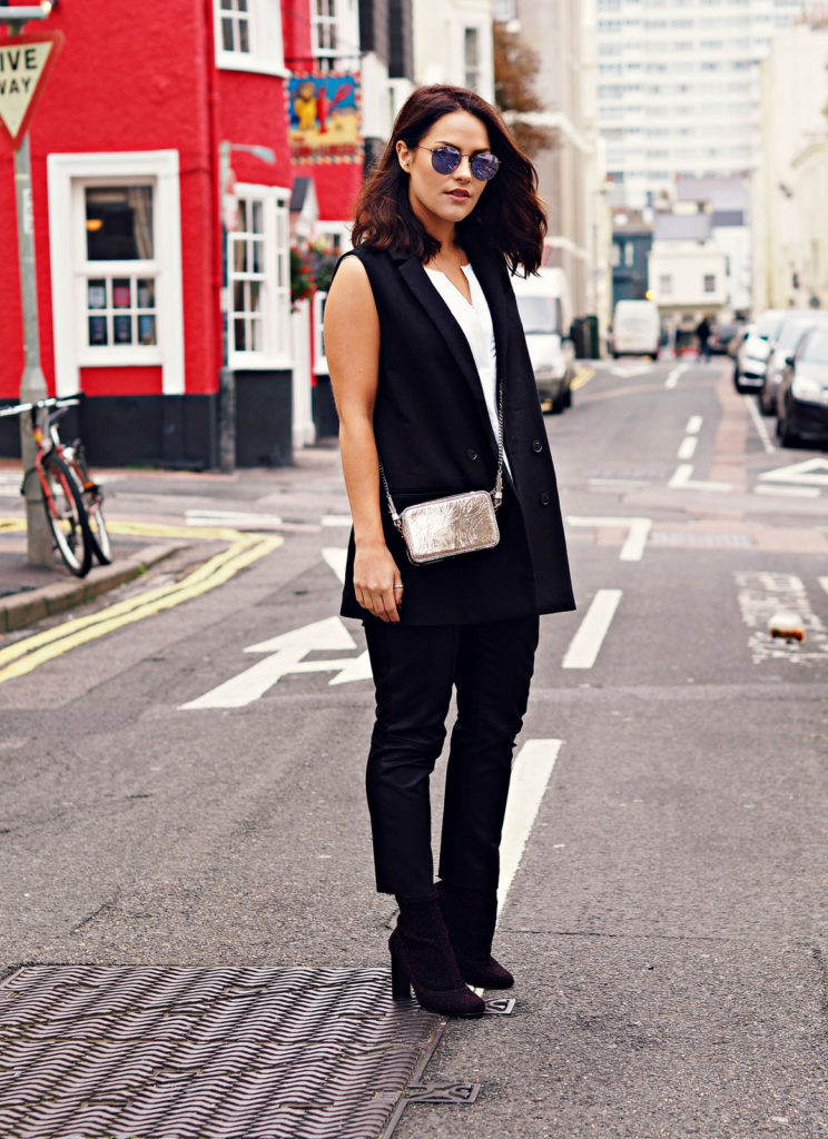 Amy Spencer wears a double breasted sleeveless jacket with leather trousers and ankle boots.   Jacket/Blouse/Trousers: Zalando at Banana Republic.