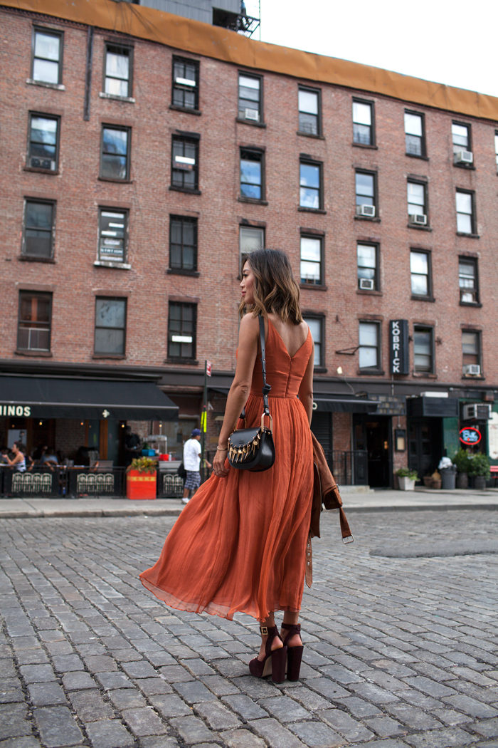 Aimee Song styles this gorgeous rust coloured dress with a detailed black bag and purple platform heels. Heels/Dress: Zimmermann, Bag: Chloe Hudson.